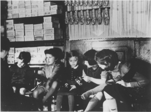 """Friedel Frankel with several children at the Erlangers' dry goods store in Guntersblum. Daughter of Lothar Erlanger is second from the right. Circa 1936. Source: """"Children Try on Shoes in the Jewish Owned Erlanger Shoe and Dry Goods Store in Guntersblum, Germany,"""" United States Holocaust Memorial Museum http://resources.ushmm.org/inquery/uia_doc.php/query/8?uf=uia_zzvIdh (accessed January 1, 2011)."""